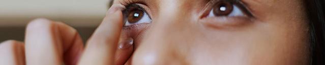 Gros plan sur une jeune femme regardant dans le miroir et enlevant ses lentilles de contact.