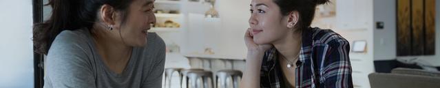 Une jeune femme parlant avec sa mère dans la cuisine.
