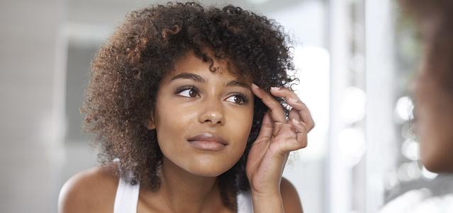 Une jeune femme regardant ses yeux en se regardant dans un miroir